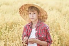 Het portret van tienerlandbouwbedrijfjongen die rood geruit overhemd dragen en geel breed-brimmed natuurlijke strohoed Stock Foto's