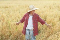 Het portret van tienerlandbouwbedrijfjongen in geruit overhemd en breed-brimmed strohoed Royalty-vrije Stock Foto's