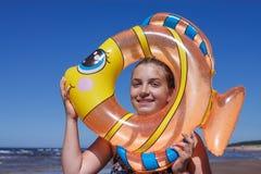 Het portret van het tienermeisje in de opblaasbare stuk speelgoed zwemmende cirkel stock foto's