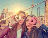 Het portret van tienermeisjes met donuts in oog New York Stock Foto