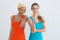 Het portret van twee het jonge vrouwelijke vrienden gesturing beduimelt omhoog Stock Fotografie