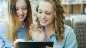 Het portret van twee jonge aantrekkelijke vrouwen gebruikt een tablet of laptop in een koffie stock videobeelden