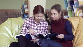 Het portret van twee mooie verraste universitaire meisjes in bibliotheek concentreerde zich op tijdschrift stock video