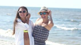 Het portret van twee vrouwen in bikini en de zomer kleden zich en zonnebril op de kust De zomervakantie, reis om te verwarmen stock footage