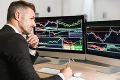 Het portret van unshaved zakenman het werken in bureau en het kijken op computer met grafiek en grafieken royalty-vrije stock fotografie
