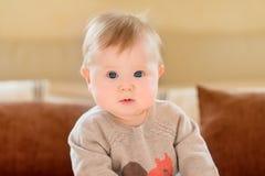 Het portret van verbaasde weinig kind met blond haar en blauwe ogen die gebreide sweaterzitting op bank dragen en camera bekijken stock fotografie