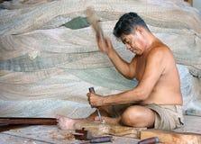Het portret van visser knipt hout bij visnetwinkel in verticaal kader. CA MAU, VIETNAM 29 JUNI Stock Foto