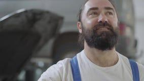 Het portret van volwassen werktuigkundige wrijft voorhoofd met zijn hand De arbeider is vermoeid na harde werkdag Gebaarde mens i stock footage