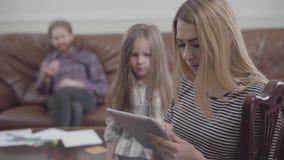 Het portret van vrij blonde vrouwenzitting met tablet in handen sluit omhoog Meisje die aandacht van haar moeder proberen te krij stock video