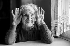 Het portret van vrolijke oude gerimpelde vrouwenholding overhandigt dichtbij haar oren Stock Foto's