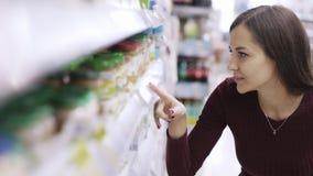 Het portret van vrouw bekijkt prijskaartjes en zoekt product op plank in supermarkt stock videobeelden
