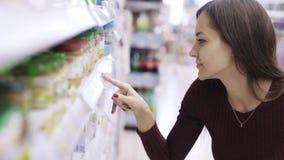 Het portret van vrouw bekijkt prijskaartjes en zoekt product in supermarkt stock video