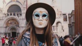 Het portret van vrouw met lang haar die hoed dragen en Carnaval maskeren status bij de kathedraal van San Marco in de langzame mo stock video