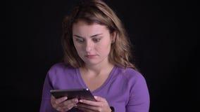 Het portret van vrouw het werken met tablet krijgt een grote schok op zwarte achtergrond stock footage