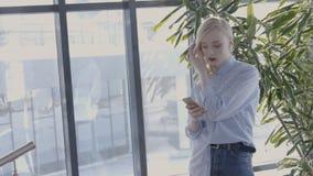 Het portret van vrouwelijke ontwerper typt messeges op haar smartphone in heldere zaal, langzame motie stock video