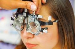 Het portret van vrouwenpatiënt in oftalmologkabinet doet oogdiagnostiek op een vage achtergrond stock afbeelding
