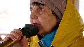 Het portret van vrouwenzeeman in regenjas spreekt in megafoon op het schip stock video