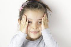 Het portret van weinig het glimlachen maakte indruk op vrolijk meisje in geruite holding haar dichtbij gezicht overhandigt Stock Foto