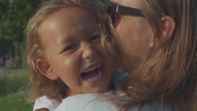 Het portret van weinig lachend kindmeisje in haar moeder ` s koestert openlucht stock videobeelden