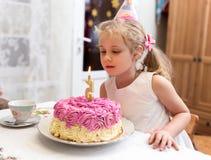 Het portret van weinig mooi meisje die met de cake van de 5 jaarverjaardag, bij lijst zitten en maakt een wens Stock Foto
