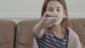 Het portret vermoeide ziek meisje zit in bank die, die thermometer bekijkt en het toont in de camera r stock footage