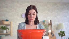 Het portret verwarde jonge vrouwenvangsten van waterdalingen van het plafond stock videobeelden