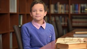 Het portretschot van de leuke schooljongen zit dichtbij het boekenrek in de bibliotheek royalty-vrije stock foto's