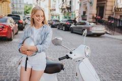 Het positief en attractiwe de jonge vrouw zitten bij de rand van nad die van de motorcyle` s zetel neer kijken Zij glimlacht Het  stock foto