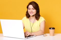 Het positief verrukte zwart haired jong wijfje die werkdag hebben, zittend bij haar werkplaats in bureau, vullend informatie in s royalty-vrije stock foto's