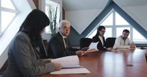 Het positieve Commerciële team van vier mensen bespreekt nieuwe ideeën stock footage