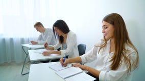 Het positieve het glimlachen mannelijke en vrouwelijke groepswerk van de studentenpraktijk en voert oefening uit stock videobeelden