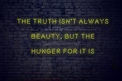 Het positieve inspirerende citaat op neonteken tegen bakstenen muur de waarheid is niet altijd schoonheid maar de honger voor het royalty-vrije stock foto