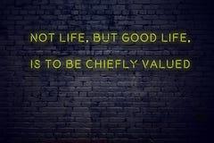 Het positieve inspirerende citaat op neonteken tegen het bakstenen muur niet leven maar het goede leven moet voornamelijk worden  royalty-vrije illustratie