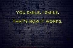 Het positieve inspirerende citaat op neonteken tegen bakstenen muur u glimlacht ik glimlacht zo het werkt royalty-vrije illustratie