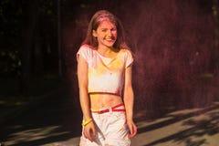 Het positieve jonge vrouw spelen met het roze droge exploderen van verfholi Royalty-vrije Stock Afbeelding