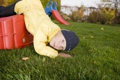 Het positieve kind legt met dia op groen gras Royalty-vrije Stock Afbeelding