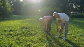 Het positieve oude paar die het uitrekken doen zich oefent in openlucht uit stock footage
