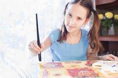 Het positieve schoolmeisje schildert thuis stock afbeeldingen