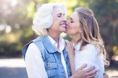 Het positieve vrouw kussen op de wang bejaarde moeder in het park Stock Afbeeldingen