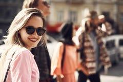 Het positieve vrouwelijke gaan rond stad met kameraden royalty-vrije stock afbeelding