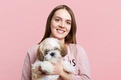 Het positieve wijfje met lang haar en tevreden uitdrukking houdt haar favoriet weinig die puppy, over roze achtergrond wordt geïs royalty-vrije stock foto