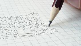 Het potlood schrijft cijfers in het notastootkussen stock video