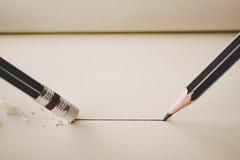 het potlood trekt een rechte lijn bij document en potloodgom het verwijderen royalty-vrije stock afbeeldingen