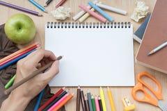 Het potlood van de handholding met Schoollevering en Witboek Stock Afbeelding