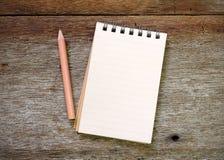 Het potlood van het notaboek op oud hout Royalty-vrije Stock Foto