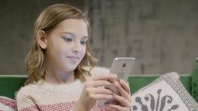 Het praatje van het tienermeisje met vriend door smartphone thuis stock video