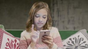 Het praatje van het tienermeisje met vriend door smartphone thuis stock footage