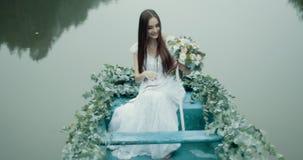 Het prachtige geheimzinnigheid het glimlachen brunette houdt het aantrekkelijke boeket van bloemen terwijl het drijven op verfraa stock video