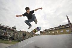 Het praktizeren van de jongen het met een skateboard rijden stock fotografie