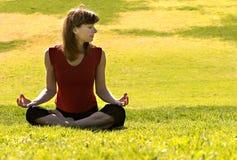 Het praktizeren van de vrouw yoga in openlucht Stock Afbeelding